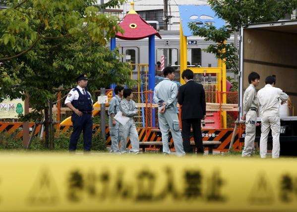 Workers of Tokyo's Toshima ward office and police officers are seen in front of playground equipment where high levels of radiation were detected at park in Toshima ward, Tokyo